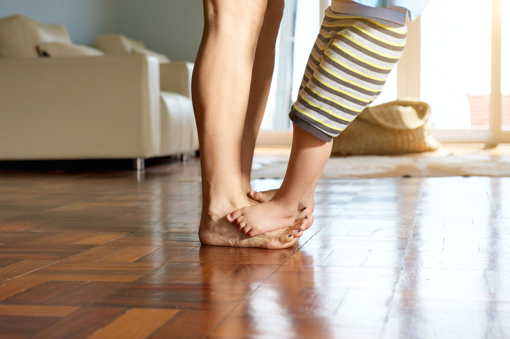 39592013 - little boy standing on mother's feet at home